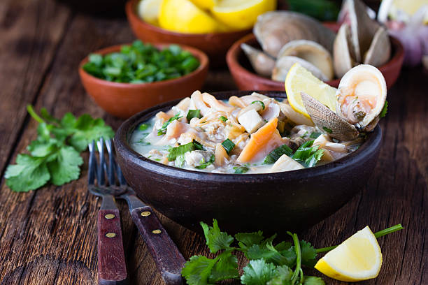 Seafood shellfish ceviche mariscal, typical dish Peru Latin America Latin American food. Seafood shellfish ceviche raw cold soup salad of seafood shellfish almejas, lemon, cilantro onion in clay bowl on wooden background. Traditional dish of Peru or Chile peruvian culture stock pictures, royalty-free photos & images