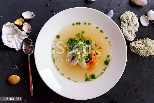 seafood soup in a white plate on a concrete background