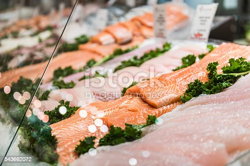 Seafood stand with cuts and filets of salmon and tuna on ice behind glass