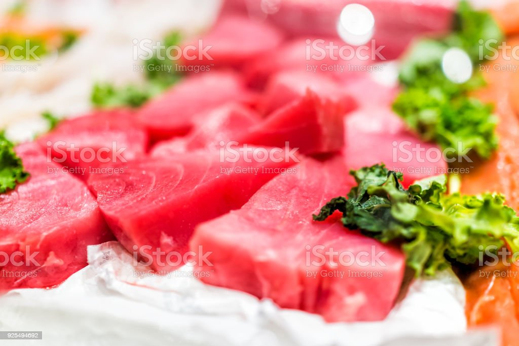 Seafood stand with cuts of red pink farmed wild tuna steaks on ice with kale leaves stock photo