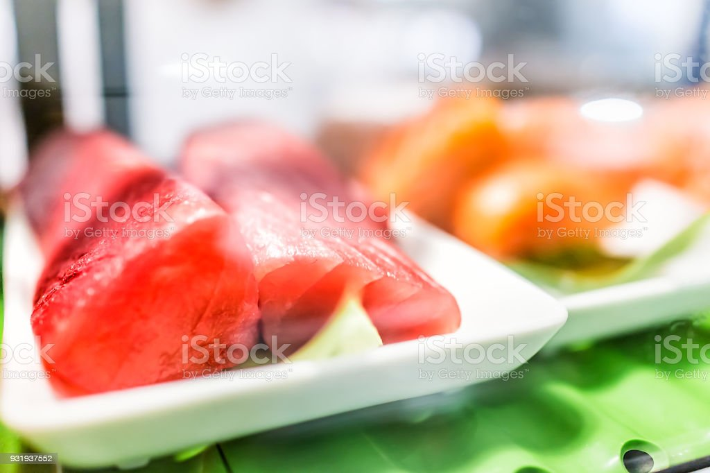Seafood stand with cuts of red pink farmed wild tuna steaks on tray plate behind glass display shelf for sashimi sushi stock photo