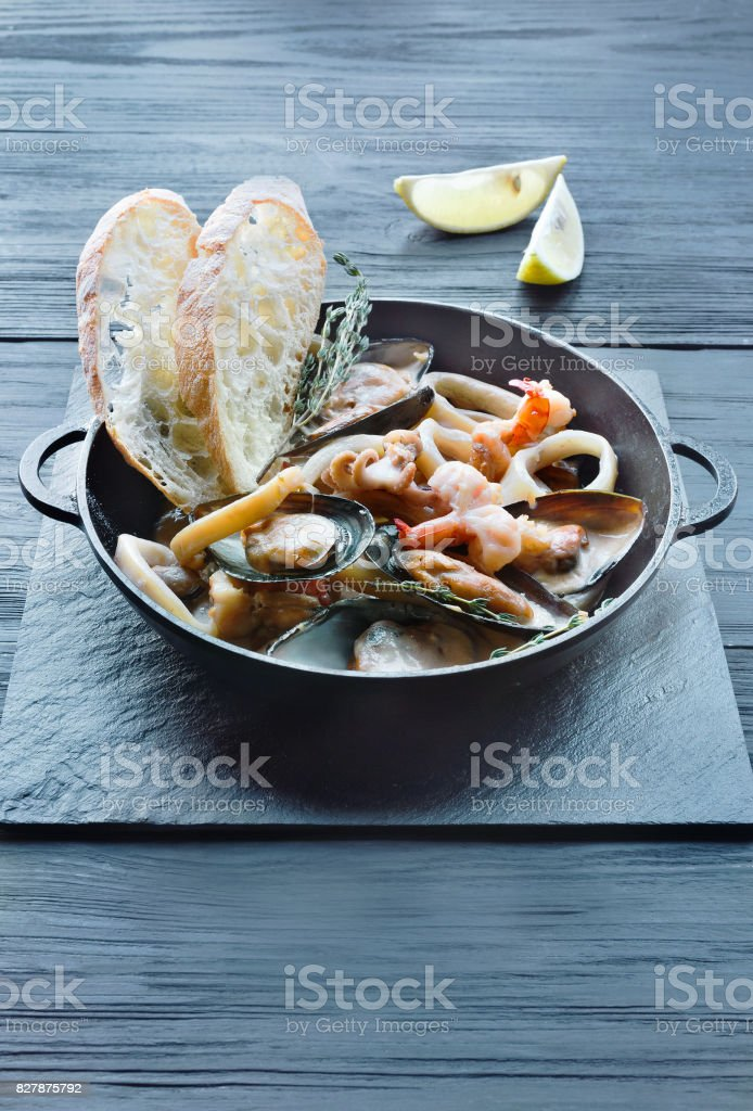 Seafood Stew in Saucepan on dark wood background stock photo