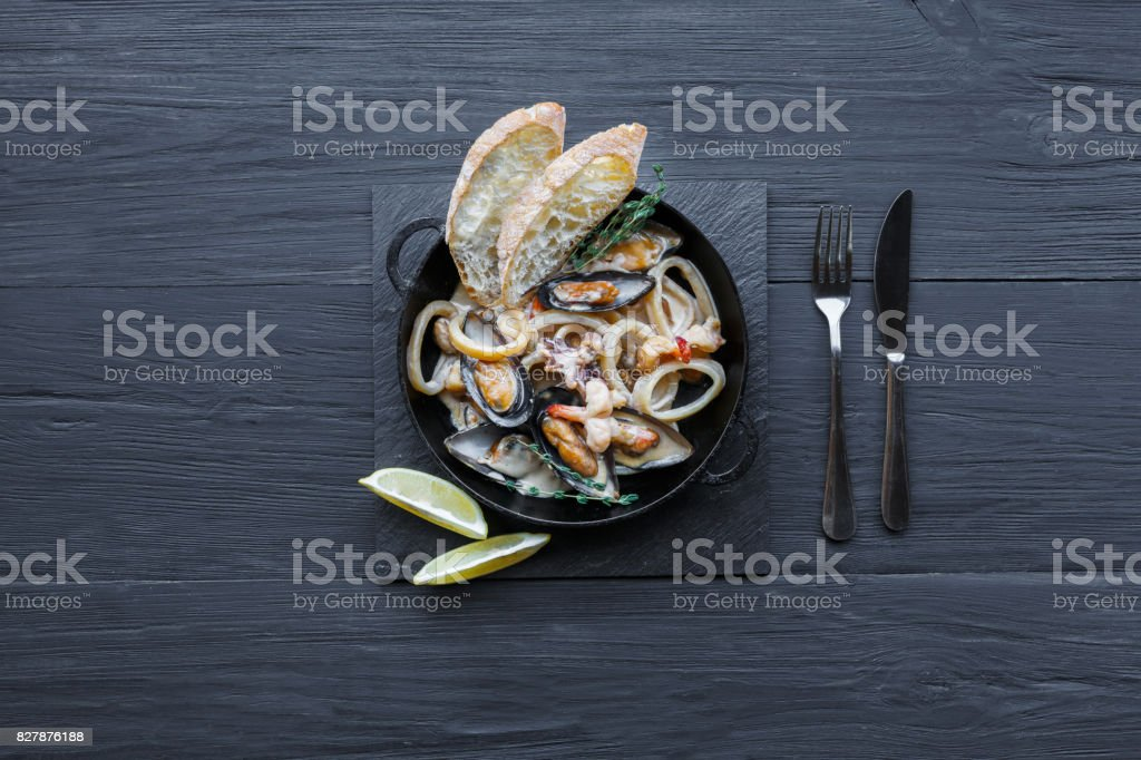 Seafood Stew on dark wood background, top view, copy space stock photo