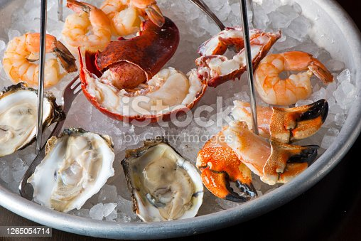 istock Seafood tower. Oysters, shrimp, lobster, crab legs, caviar. Fresh oysters served with shallots and cocktail sauce, mignonette sauce and fresh lemons and limes. Classic American steakhouse or French bistro appetizer. 1265054714