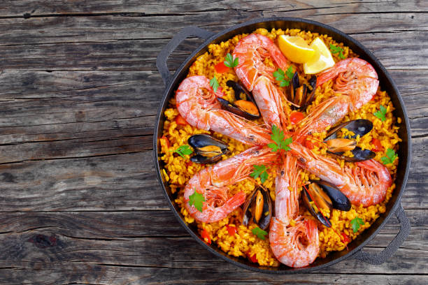 seafood valencia paella with king prawns delicious seafood valencia paella with king prawns, mussels on savory saffron rice with spices and lemon wedges in pan, on wooden table, traditional spanish cuisine, view from above, close-up arroz stock pictures, royalty-free photos & images