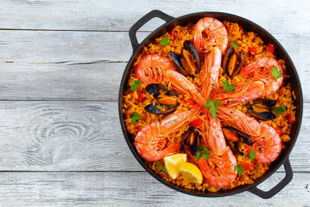 seafood valencia paella with king prawns delicious seafood valencia paella with king prawns, mussels on savory creamy saffron rice with spices and lemon wedges in pan, on old wooden table, authentic recipe,view from above arroz stock pictures, royalty-free photos & images