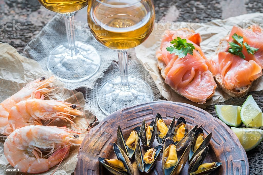Seafood with two glasses of wine on the wooden table stock photo