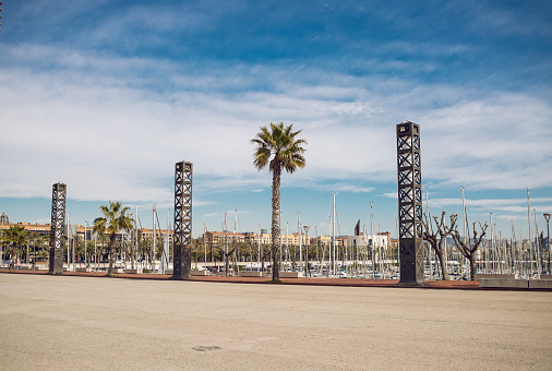 Seafront in Barcelona with Palms and Lanterns. Blue Sky.