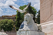 Marble lions and fountains surround an old obelisk in the center of Piazza Popolo, Rome, Italy
