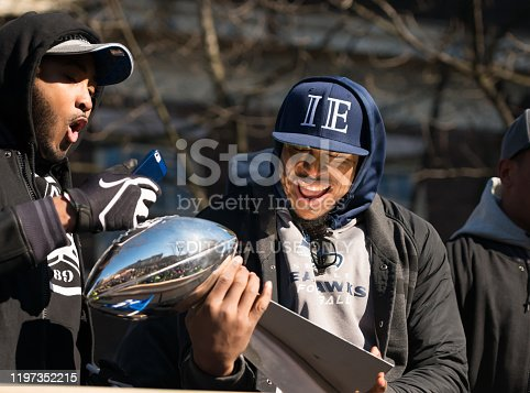 Seattle, USA - February 5th, 2014: Bobby Wagner early in the day holding the Lombardi Trophy with Kenneth Bernard Wright during the Seahawks homecoming parade on 4th avenue after the XLVIII Super Bowl win.