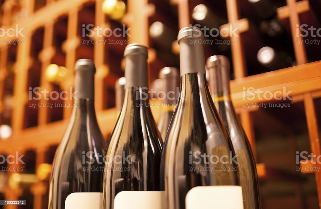 Sealed glass wine bottles in wine cellar stock photo