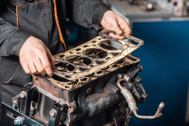Sealing gasket in hand. The mechanic disassemble block engine vehicle. Engine on a repair stand with piston and connecting rod of automotive technology. Interior of a car repair shop. stock photo