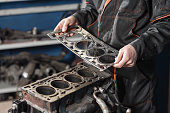 istock Sealing gasket in hand. The mechanic disassemble block engine vehicle. Engine on a repair stand with piston and connecting rod of automotive technology. Interior of a car repair shop. 903184508