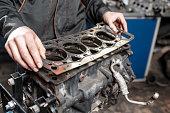 istock Sealing gasket in hand. The mechanic disassemble block engine vehicle. Engine on a repair stand with piston and connecting rod of automotive technology. Interior of a car repair shop. 903184540