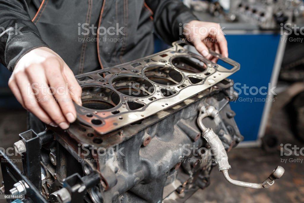 Dichtung Dichtung in der hand. Die mechanische Demontage Block Motor Fahrzeug. Motor auf eine Reparatur stehen mit Kolben und Pleuel der Kfz-Technik. Innenraum einer Autoreparaturwerkstatt. – Foto