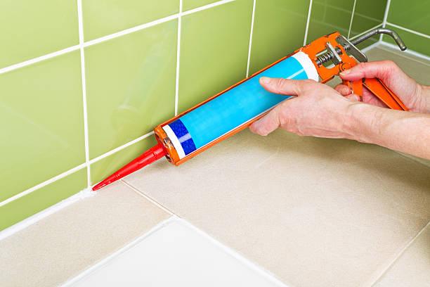 Sealing shower tiles with caulk gun stock photo