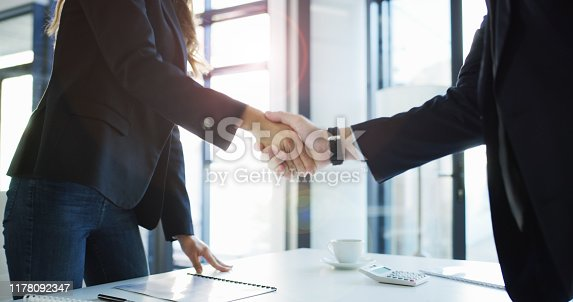 Cropped shot of two unrecognizable businesspeople standing and shaking hands after a successful meeting in the office