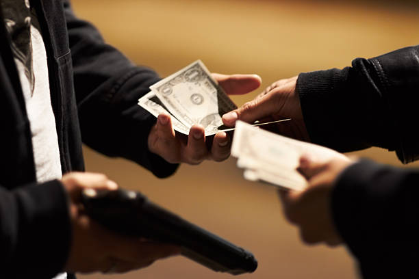 Sealing the deal Hands holding cash and a gun passing money between them drug dealer stock pictures, royalty-free photos & images