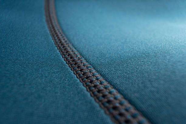 Seam of a blue neoprene diving wetsuit Close up of stitching along the seam of a blue neoprene diving wetsuit wetsuit stock pictures, royalty-free photos & images