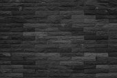 Seamless Black pattern of decorative brick sandstone wall surface with concrete of modern style design decorative uneven have cracked realmasonry wall of multicolored stones or blocks with cement.