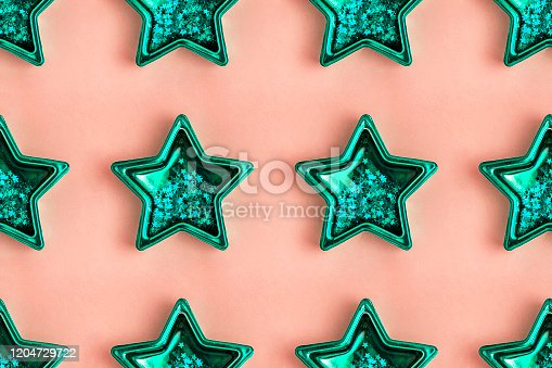 istock Seamless pattern from five pointed mint metallic star on pink surface 1204729722