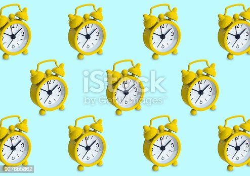 istock Seamless pattern made of golden analogue clocks in isolated blue pastel background 927655862