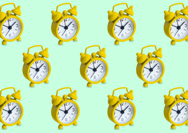 Seamless pattern made of golden analogue clocks in isolated green pastel background stock photo
