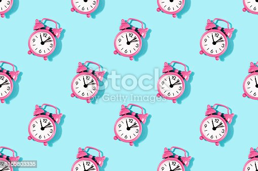 istock Seamless pattern made with pink alarm clock on turquoise background. 1155803335