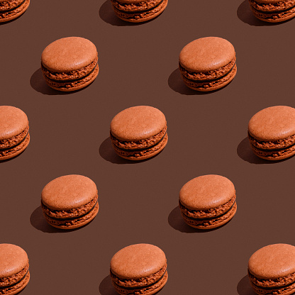 Seamless pattern of brown chocolate macaroons on brown background. Sweet And Colourful French cookies Macaroons. Sweet background, concept.