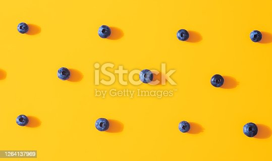 867774250 istock photo Seamless pattern with fresh sweet blueberry fruit on colorful yellow background. Dessert healthy food concept. Raw summer diet. Delicious nature vegetarian ingredient. Flat lay, minimal style 1264137969