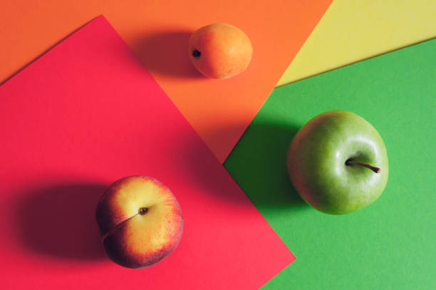 Seamless pattern with green apple,peache and apricot. Fruits abstract background. Apple on the green background, peaches on red background and apricot on orange background. - Image stock photo