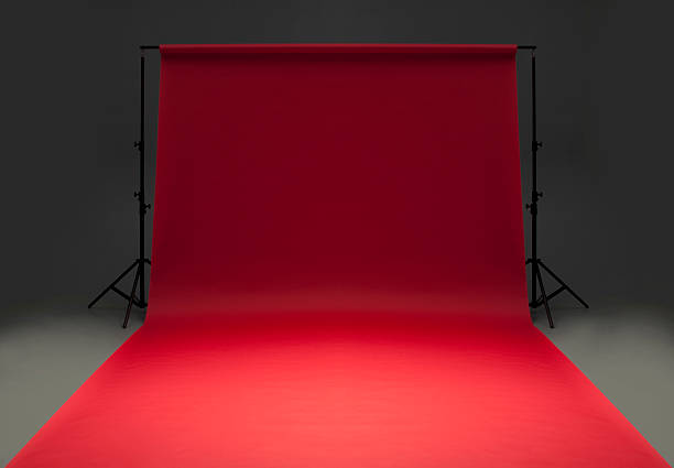 Seamless red background paper hanging on stands-isolated on grey stock photo
