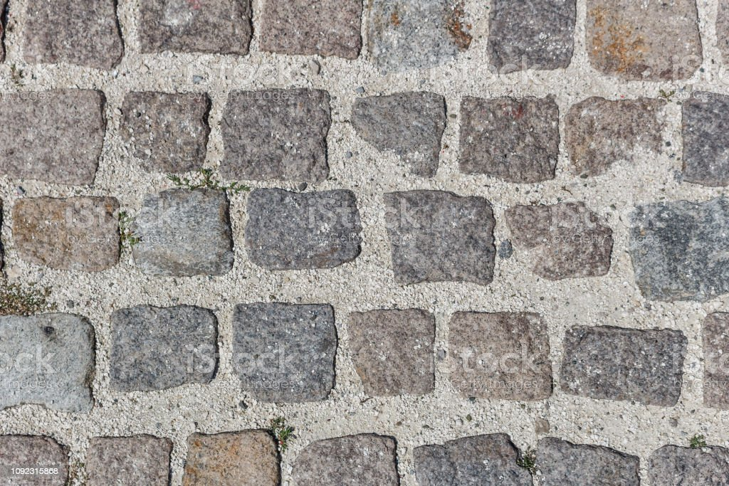 Seamless texture of old square granite stone pavement with big gaps...