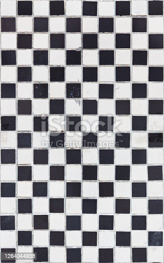 Seamlessly tileable black and white checkered grunge tile background.
