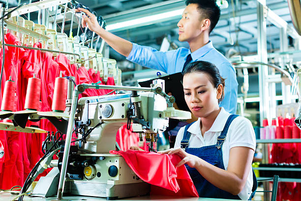 Seamstress and shift supervisor in textile factory stock photo