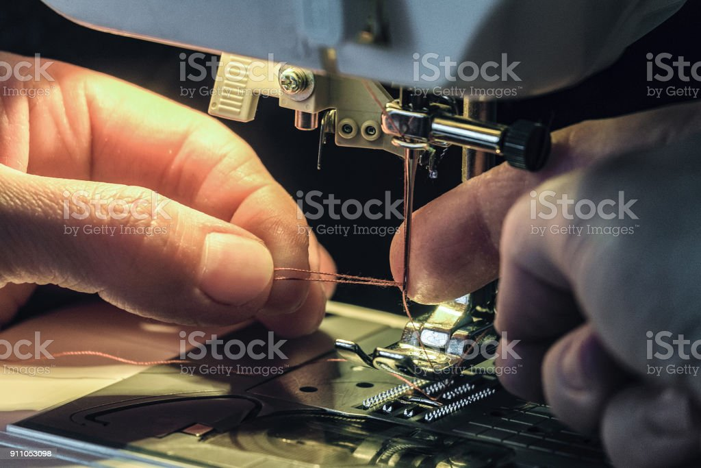 Seamstress inserts the thread through the needle threader of the sewing machine. Work by the light of the built-in hardware lamp. Steel needle with looper and presser foot close-up. stock photo