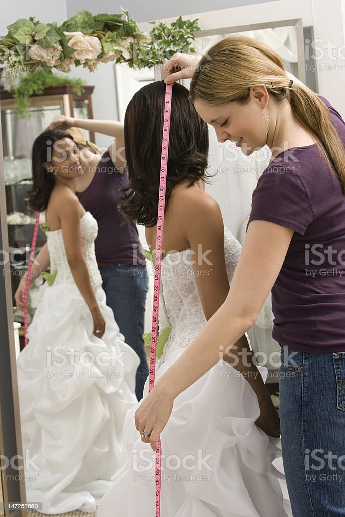 Seamstress measuring bride. stock photo