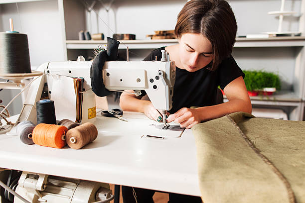 seamstress  put thread in needle. tailor's workplace - embroidery machine stock pictures, royalty-free photos & images