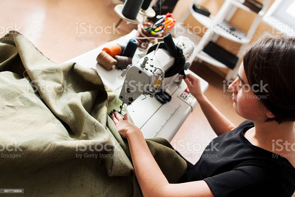 seamstress sews clothes. Workplace of tailor stock photo