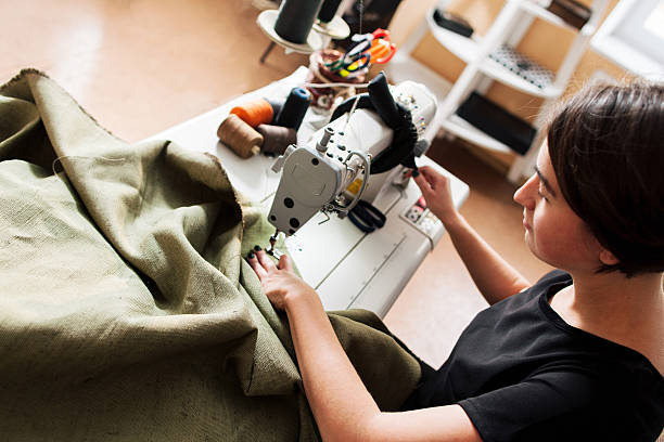 seamstress sews clothes. workplace of tailor - sewing machine needle stock photos and pictures
