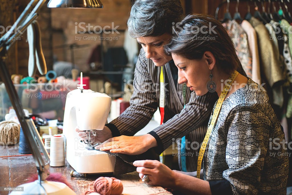 Seamstress Teaching her Assistant how to Use the Sewing Machine stock photo