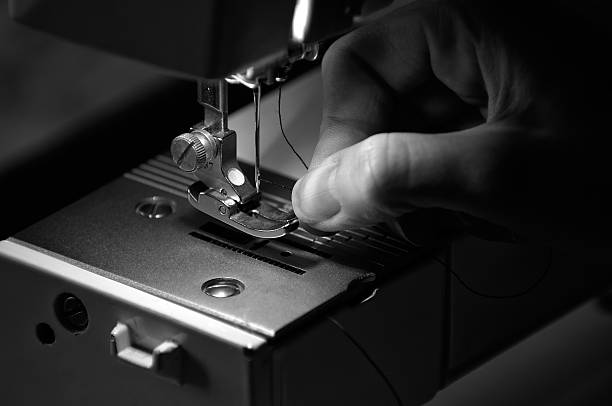 seamstress threading a sewing machine - sewing machine needle stock photos and pictures