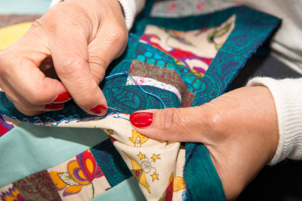 seamstress woman sewing for finish a quilt. - quilt stock photos and pictures