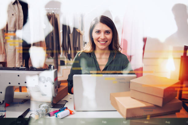 Seamstress works to new clothes ordered by internet client stock photo