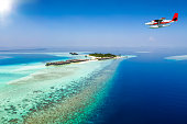Aerial view of a seaplane approaching a tropical island in the Maldives with calm sea and sunshine