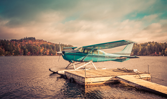 Seaplane docked at the shore awaiting leaf-peepers and adventure seekers, retro split tone