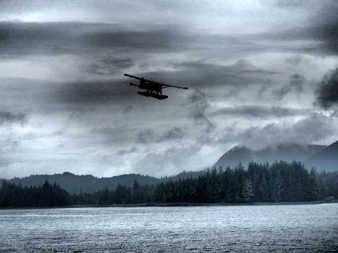 Seaplane silhouette in a cloudy sky
