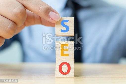 Search engine optimisation concept. Hand putting wood block cube shape with word SEO