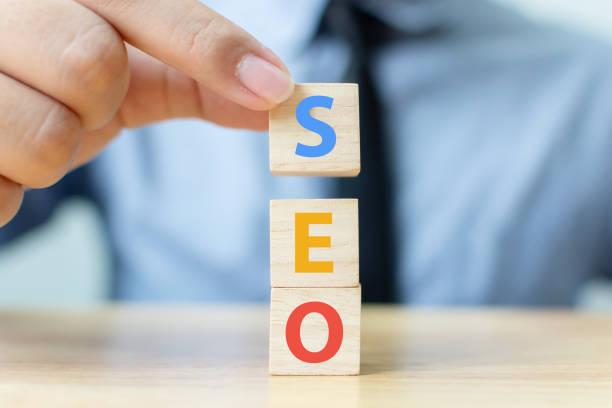 concepto de optimización de motores de búsqueda. mano poniendo la forma del cubo del bloque de madera con la palabra seo - seo fotografías e imágenes de stock