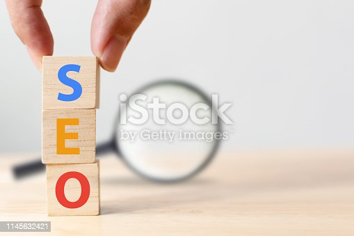 istock Search engine optimization concept. Hand putting wood block cube shape with word SEO and magnifying glass 1145632421